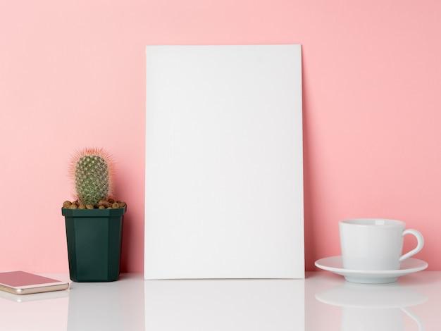 Leeg wit frame en plant cactus, kopje koffie of thee op een witte tafel tegen de roze muur