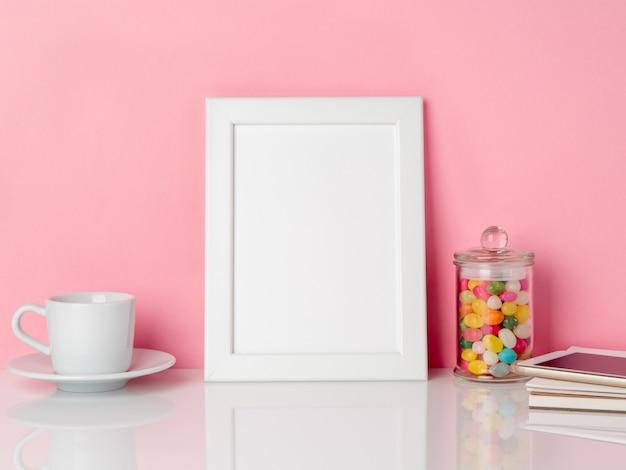 Leeg wit frame en snoepjes in pot, kopje koffie of thee op een witte tafel tegen de roze