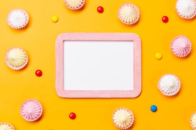 Leeg wit frame omgeven met kleurrijke edelstenen en aalaw op gele achtergrond Gratis Foto