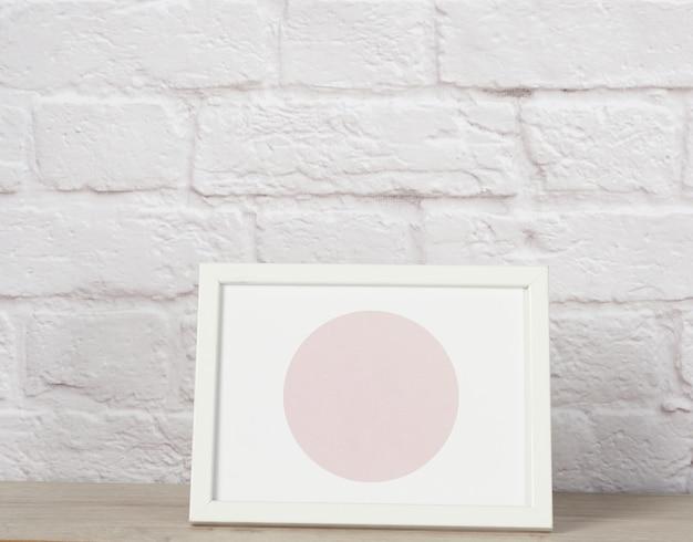 Leeg wit houten fotokader, witte bakstenen muur