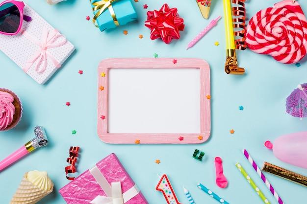Leeg wit houten frame dat met verjaardagspunten wordt verfraaid op blauwe achtergrond