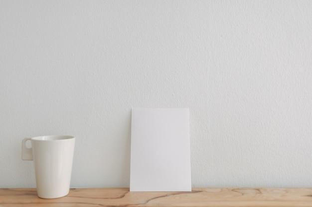Leeg wit kaartmodel leun op een theekop met witte muur