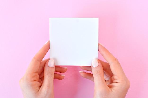 Leeg wit papier in vrouwelijke handen op een roze achtergrond, als mockup voor uw ontwerp. minimale compositie in platliggende stijl.