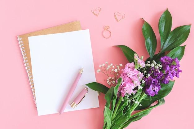 Leeg wit vel op spiraal gouden kladblok met paperclip hart en ring en boeket bloemen op roze achtergrond.