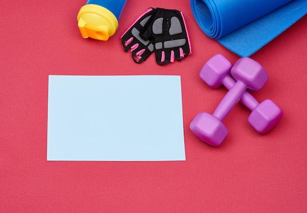 Leeg wit vel papier en een paar paarse plastic halter, handschoenen en een blauwe sportmat
