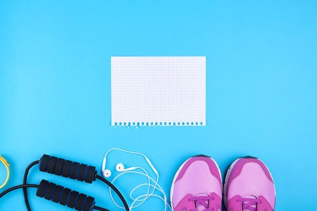 Leeg wit vel papier, roze sport sneakers en springtouw op een blauwe ondergrond
