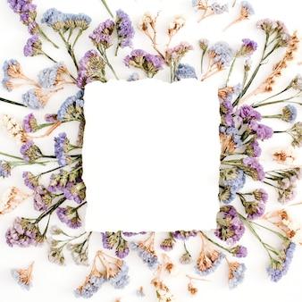 Leeg witboek leeg op blauw en paars gedroogde bloemen frame op witte achtergrond. platliggend, bovenaanzicht