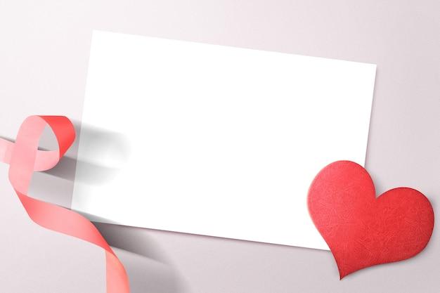 Leeg witboek met hart en lint op een gekleurde muur. valentijnsdag. lege ruimte voor exemplaarruimte