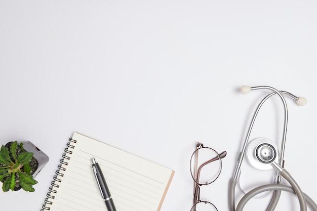 Leeg witboek van notitieboek met zwarte inktpen, stethoscoop, pen en leeg receptblok. geneeskunde of apotheek. leeg medisch formulier klaar voor gebruik. moderne medische informatietechnologie.
