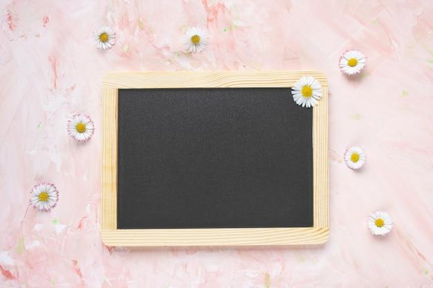Leeg zwart berichtbord en verse lentebloemen op lichtroze gestructureerde achtergrond