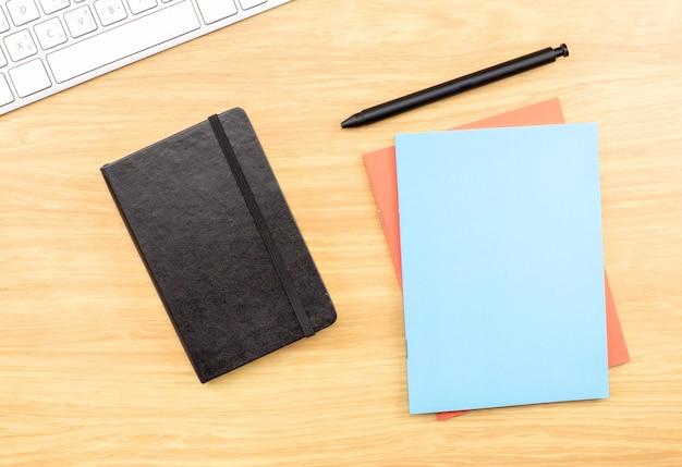 Leeg zwart, blauw en oranje notitieboekje, pen en toetsenbord op houten lijst