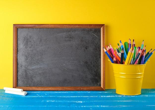 Leeg zwart krijtkader, wit krijt en schoolbenodigdheden