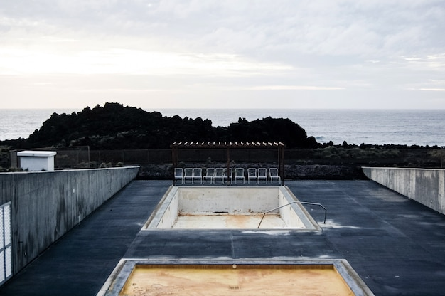 Leeg zwembad met stoelen in de buurt van de klif en een zee