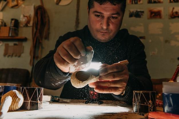 Leer houtsnijwerk onder licht in het atelier