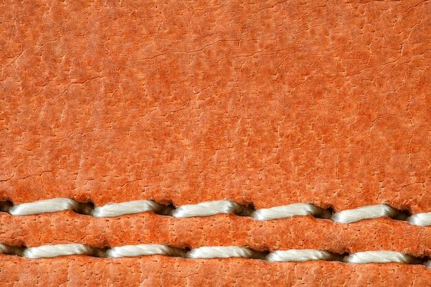 Leer is natuurlijk oranje, naad is gemaakt van witte draden, close-up macroweergave