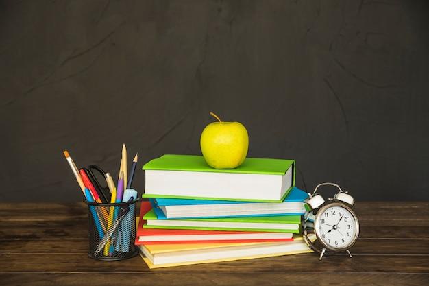Leerboeken met potloodkop en klok op lijst