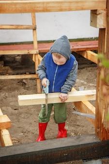 Leergierig jongetje zagen een houten plank. woningbouw. kleine helper. kleine bouwer.