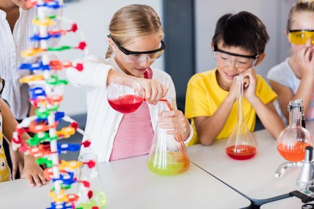 Leerling doet wetenschap terwijl klasgenoten haar kijken