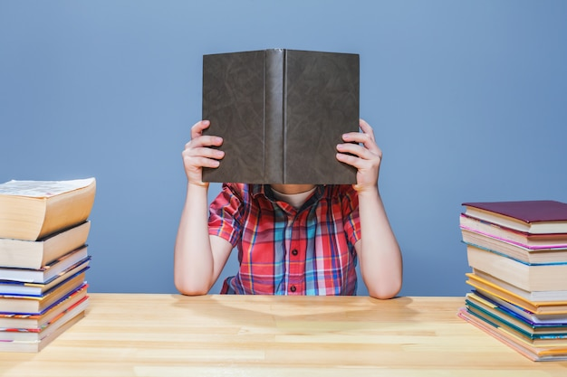 Leerling met bril die kennis uit een leerboek haalt