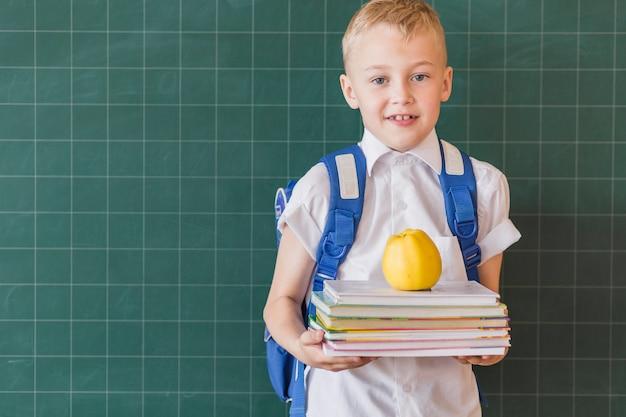 Leerling met rugzak en handboeken in klaslokaal