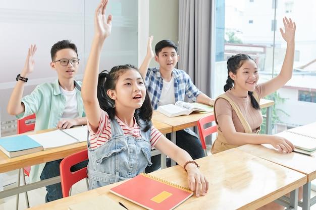 Leerlingen die hun hand opsteken omdat ze de vraag van de leraar willen beantwoorden