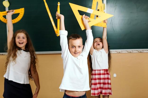 Leerlingen met apparatuur op schoolbord