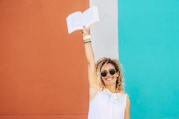 Lees en lees een papieren boek om te studeren of te ontspannen in het concept van vrijetijdsactiviteiten met een volwassen mooie blanke blonde krullende vrouw die het boek opgeeft