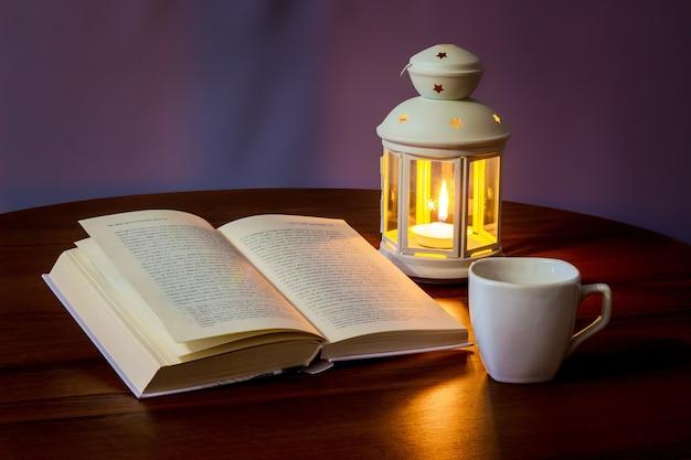 Lees het boek in het licht van een lantaarn met een kopje koffie of thee