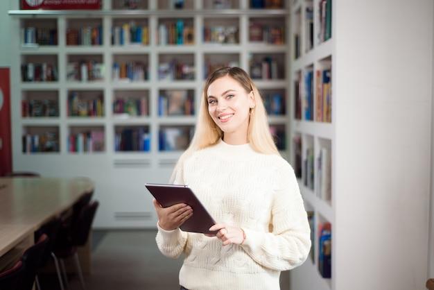 Leesboek in bibliotheek. student in de bibliotheek met een boek in haar handen.