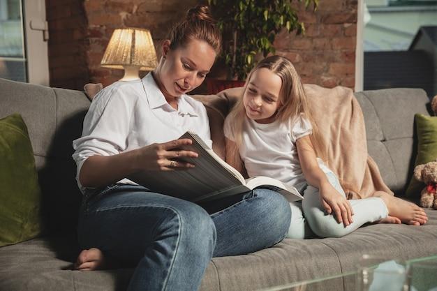 Leesboek. moeder en dochter tijdens zelfisolatie thuis terwijl ze in quarantaine zijn, familietijd gezellig en comfortabel, huiselijk leven. vrolijke en gelukkig lachende modellen. veiligheid, preventie, liefdesconcept.
