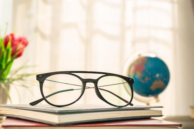 Leesbril op hardcover boeken boven houten tafel naast het raam