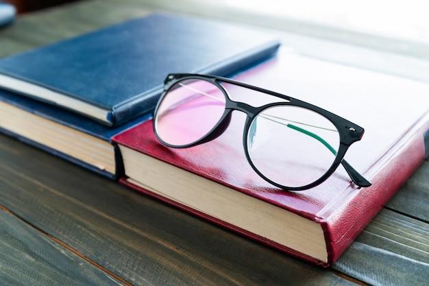 Leesbril op hardcover boeken boven houten tafel