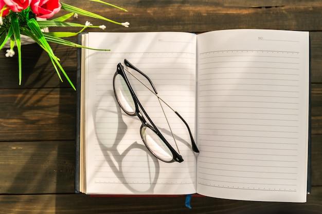 Leesbril op open boek gezet over houten tafel