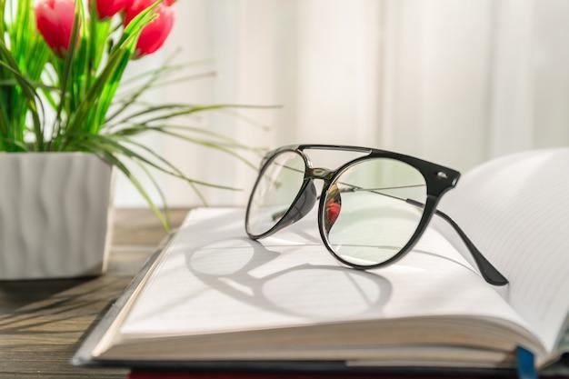 Leesbril op open boeken boven houten tafel naast het raam