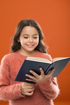 Leesoefening voor kinderen. meisje houdt boek gelezen verhaal over oranje achtergrond. kind geniet van het lezen van boek. boekwinkelconcept. prachtige gratis kinderboeken beschikbaar om te lezen. kinderboeken.
