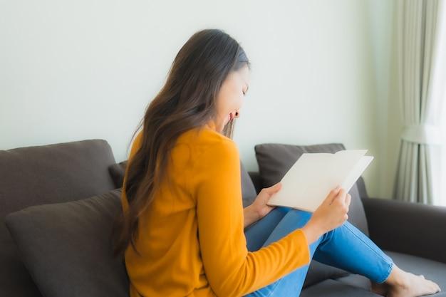 Leest het portret jonge aziatische vrouw boek op bankstoel met hoofdkussen in woonkamer