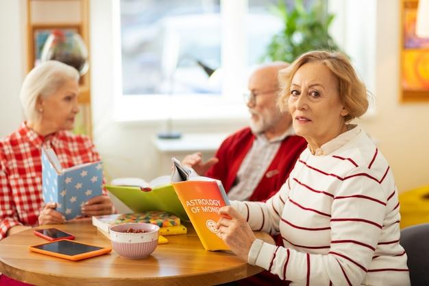 Leestijd. ernstige oudere vrouw die aan tafel zit met een boek terwijl ze het leest