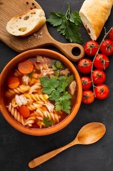 Leg de wortelen en fusilli van broccoli plat in een kom met brood op snijplank en houten lepel