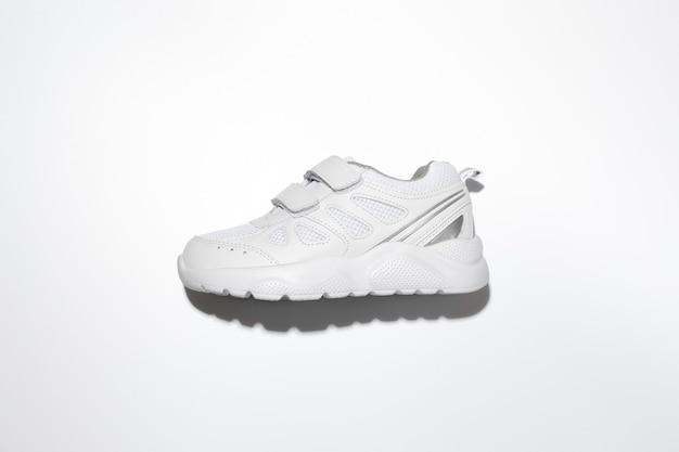 Leg een witte hardloopschoen voor kinderen plat met klittenband aan de zijkant met harde schaduwen in het midden...