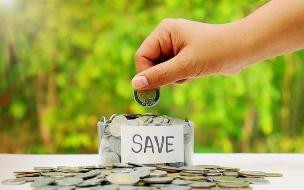 Leg en leg munten in een spaarvarken op een natuurlijke achtergrond. concepten, groei en besparingen.