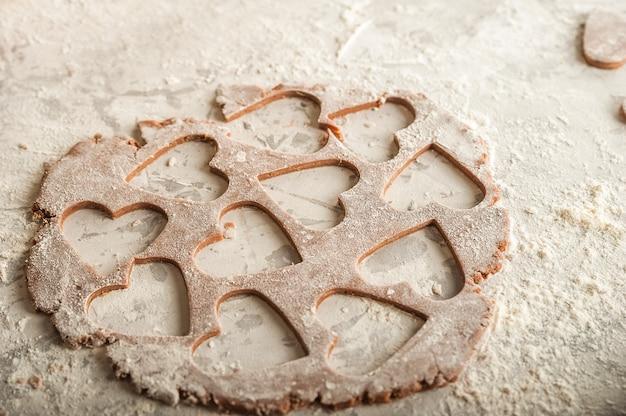 Leg het bloemhartdeeg plat. textuur van het deeg voor koekjesclose-up. peperkoekdeeg op 14 februari, bloem, deegrol en kopie ruimte.