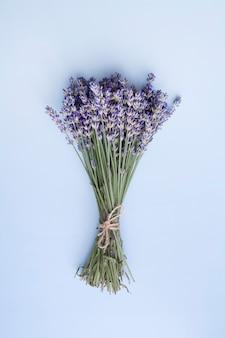 Leg lavendelbloemen plat in een bos op een blauwe ondergrond