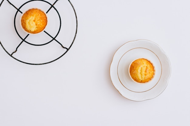 Leg oranje muffins op een metaaltribune en een plaat plat