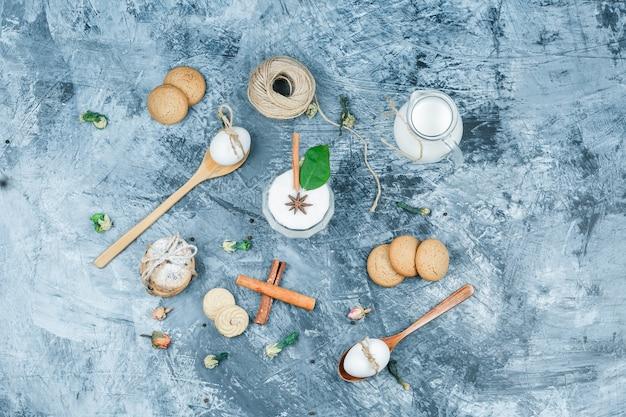 Leg plat een kan melk en een glazen kom yoghurt met lepels, koekjes, eieren, kluwen, kaneel en een plant op een donkerblauw marmeren oppervlak. horizontaal