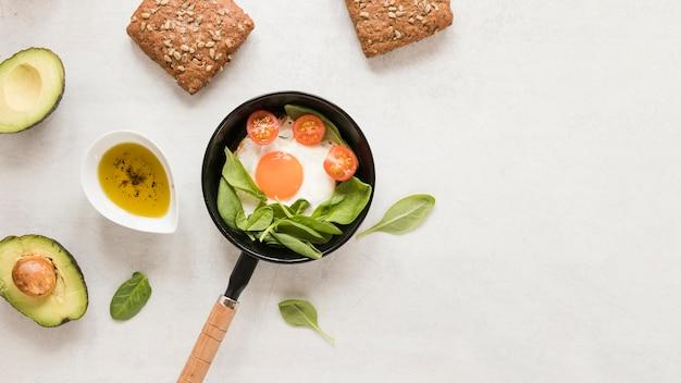 Leg plat gebakken ei in pan met tomaten en avocado