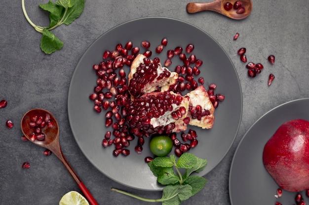 Leg plat granaatappel op plaat met munt en lepel
