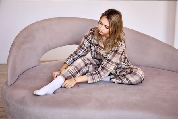 Legante vrouw in pyjama zit thuis op bed