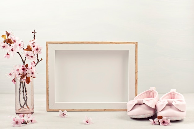 Lege afbeeldingsframe, roze tedere lentebloemen en kleine baby meisje schoenen