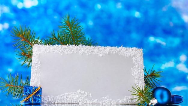 Lege ansichtkaart, kerstballen en spar op blauwe achtergrond