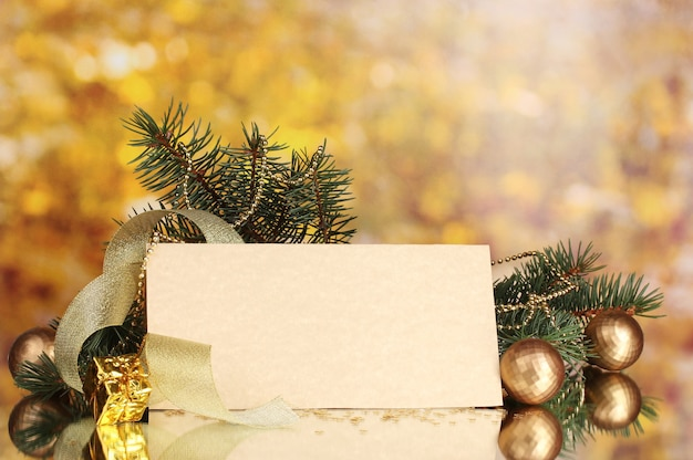 Lege ansichtkaart, kerstballen en spar op gele achtergrond